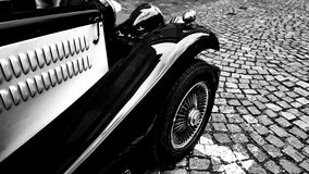 葡萄酒经典黑旧车改装的高速马力汽车汽车的前方零件在大卵石路的 免版税库存照片