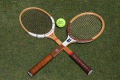葡萄酒网球拍和Slazenger Wimbledon网球在草网球场 免版税库存照片