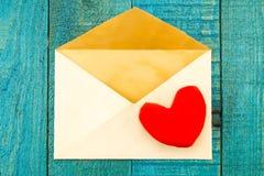 葡萄酒老信封有红色心脏蓝色木背景 库存图片