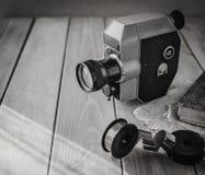 葡萄酒老电影摄影机和影片轴在一张木桌,旧书,clothl上 减速火箭的照片 复制空间 免版税库存图片