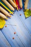葡萄酒背景上色了铅笔秋天果子蓝色桌 免版税库存图片