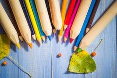 葡萄酒背景上色了铅笔秋天果子蓝色桌 免版税图库摄影
