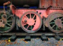 葡萄酒蒸汽引擎的轮子在红色的 免版税库存图片