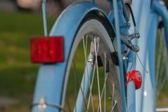 葡萄酒蓝色夫人在城市公园骑自行车部分后面光 库存图片