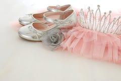 葡萄酒薄纱桃红色薄绸的礼服、冠和银鞋子在木白色地板上 免版税图库摄影