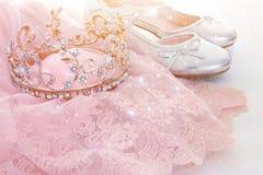 葡萄酒薄纱桃红色薄绸的礼服、冠和银鞋子在木白色地板上 库存图片