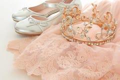 葡萄酒薄纱桃红色薄绸的礼服、冠和银鞋子在木白色地板上 免版税库存照片