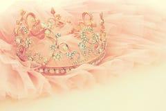 葡萄酒薄纱桃红色薄绸的礼服和金刚石冠状头饰在木白色桌上 婚礼和girl& x27; s党概念 库存照片