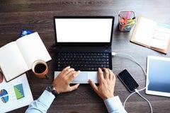 葡萄酒行家木桌面顶视图,使用膝上型计算机的男性手 免版税库存图片