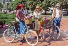 葡萄酒衣物的妇女有见面在节日减速火箭的巡航开始前的老自行车的 库存图片