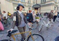 葡萄酒衣物的年轻逗人喜爱的妇女准备好循环在老自行车在时尚节日减速火箭的巡航 免版税库存图片