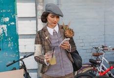 葡萄酒衣物的美丽的少妇有手机和减速火箭的自行车的准备好循环 库存照片