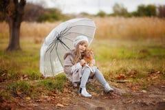 葡萄酒衣裳的女孩有一只红色猫和一把透明伞的在步行在秋天公园 免版税库存图片