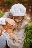 葡萄酒衣裳的女孩有在步行的一只红色猫的在秋天公园 库存图片