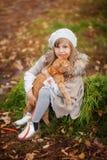 葡萄酒衣裳的女孩有在步行的一只红色猫的在秋天公园 免版税库存照片