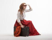 葡萄酒衣裳的妇女坐手提箱并且调查距离 免版税库存照片