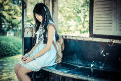 葡萄酒衣裳的逗人喜爱的亚裔泰国女孩单独等待 免版税库存图片