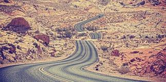 葡萄酒被定调子的弯曲的沙漠高速公路 免版税库存图片