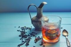 葡萄酒被射击与过滤器、水罐、茶匙和叶子的茶玻璃 免版税库存图片