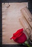 葡萄酒被捆绑的纸在木滚动红色玫瑰 免版税库存照片
