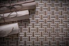 葡萄酒被编织的木表面上的滚动的羊皮纸 免版税库存图片