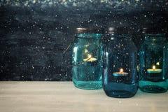 葡萄酒装饰不可思议的金属螺盖玻璃瓶的图象有蜡烛光的在木桌上 闪烁覆盖物 免版税库存照片
