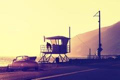 葡萄酒过滤了在海滩的日落与救生员塔 免版税库存图片