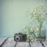 葡萄酒过滤了并且定了调子新鲜的白花和老照相机的图象在木桌 库存图片