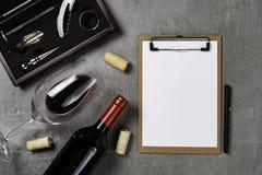 葡萄酒酿造学的辅助部件 杯用在具体背景和笔记薄的酒 r 库存图片