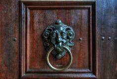 葡萄酒金属在一个棕色木门的通道门环 库存图片