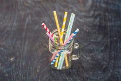 葡萄酒金属螺盖玻璃瓶和多彩多姿的螺旋秸杆 婚礼装饰概念 甜表 与饮料概念的一张桌 库存照片