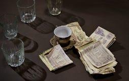 葡萄酒金钱、玻璃和咖啡杯在木桌上 图库摄影