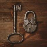 葡萄酒钥匙和锁在木背景 免版税图库摄影