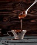 葡萄酒银色杯子液体巧克力和匙子用流动的巧克力 库存图片
