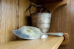 葡萄酒银色桨和冰桶有钳子的在架子 免版税库存图片