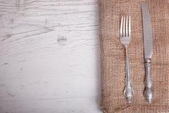 葡萄酒银色碗筷刀子和叉子在餐巾,在老 库存图片