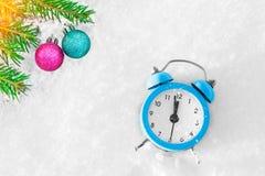 葡萄酒闹钟、圣诞树分支和装饰在雪在日落 免版税库存图片