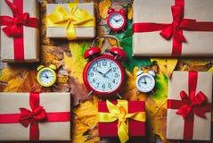 葡萄酒闹钟和槭树叶子有节日礼物的 免版税库存图片
