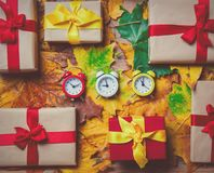 葡萄酒闹钟和槭树叶子有节日礼物的 免版税库存照片