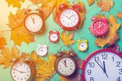 葡萄酒闹钟和槭树叶子 免版税库存照片