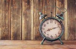 葡萄酒闹钟的图象在木桌上的在木背景前面 被过滤的减速火箭 库存图片