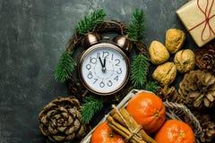 葡萄酒闹钟被设置到五周详了对午夜 新年` s前夕读秒 潘斯锥体核桃蜜桔肉桂条礼物 免版税库存图片