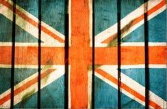 葡萄酒难看的东西过滤了,在木背景的英国旗子 免版税库存照片