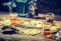 葡萄酒非法赌博的桌用伏特加酒、香烟和卡片 库存照片