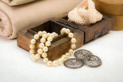 葡萄酒鞋带、银色按钮和珍珠项链 库存照片