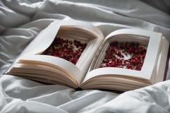 葡萄酒预定与在一张白色床上的干红色花 概念乡愁和记忆葡萄酒背景 免版税库存图片