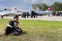 葡萄酒飞行员制服的人微笑与瑞士Pilatus特技队P3飞行物的在背景中 免版税库存图片