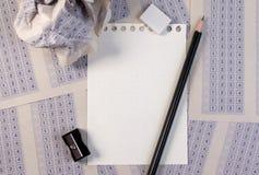 葡萄酒经典答案纸被弄皱的纸球与铅笔、磨削器和纸减少的 库存图片