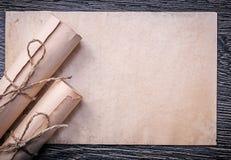 葡萄酒滚动被捆绑的纸在木背景 免版税库存照片