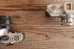 葡萄酒35mm影片照相机说谎在标日期的木背景的两个 免版税库存图片